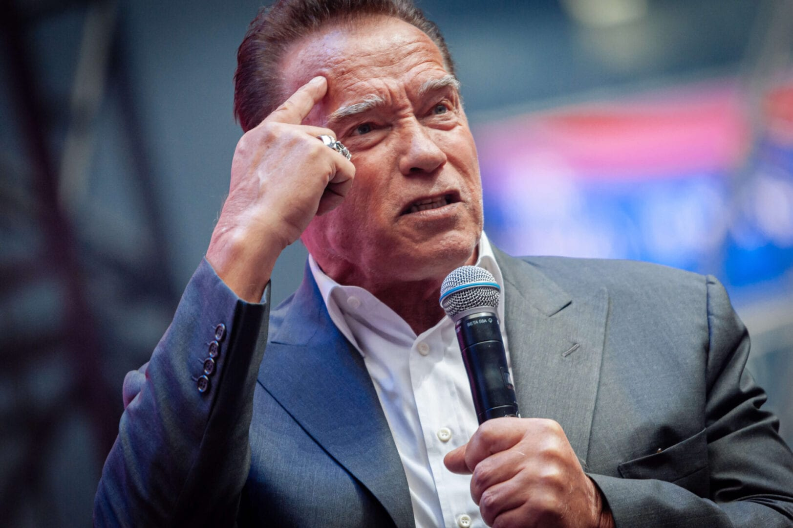 Arnold Schwarzenegger talking at event and pointing to head