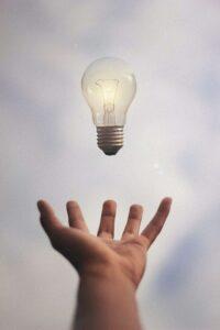 Hand reaching for light bulb