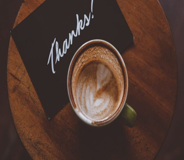 Coffee latte in teacup on table with thanks note