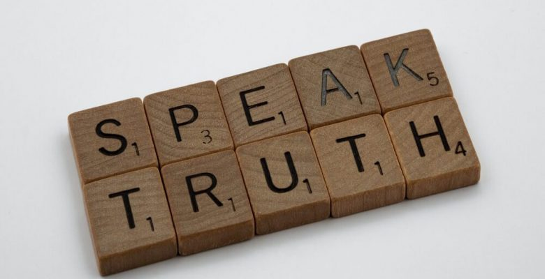 Brown wooden blocks on white table with speak truth text