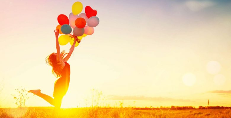 woman jumping in air and letting go of colourful balloons