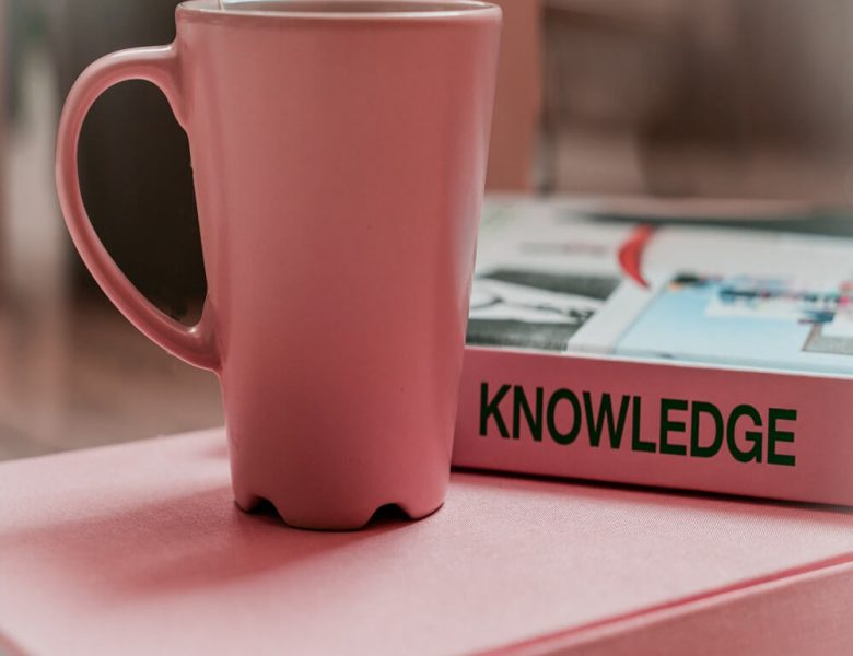 Pink mug next to book titled knowledge