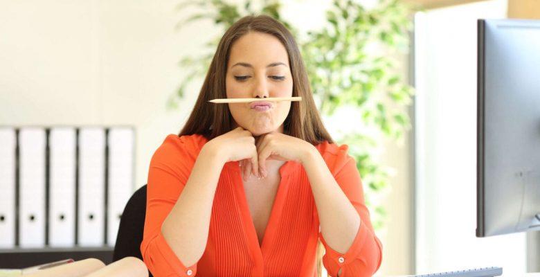 bored woman balancing pencil on nose