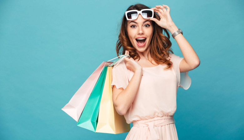 young woman happy carrying shopping bags
