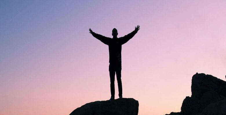 Man at sunset standing on rock with arms outstretched