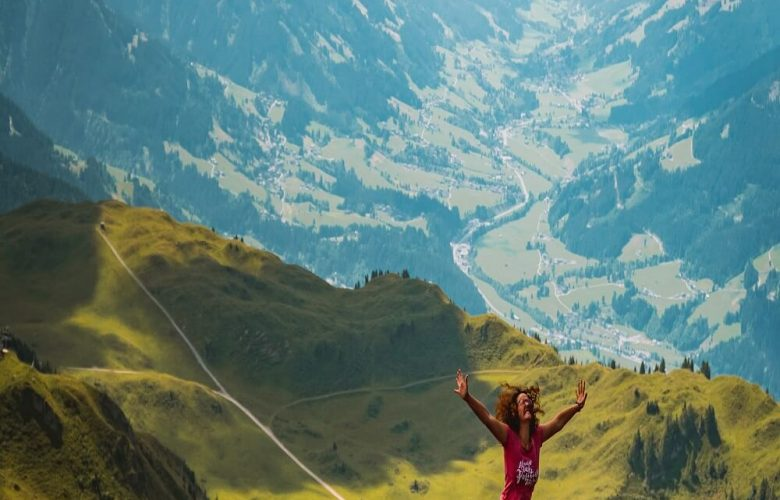 Woman jumping on hill during daytime