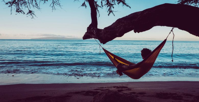 person relaxing in hammock overlooking beach