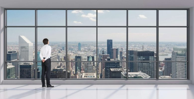 businessman looking out window with stunning view of entire city