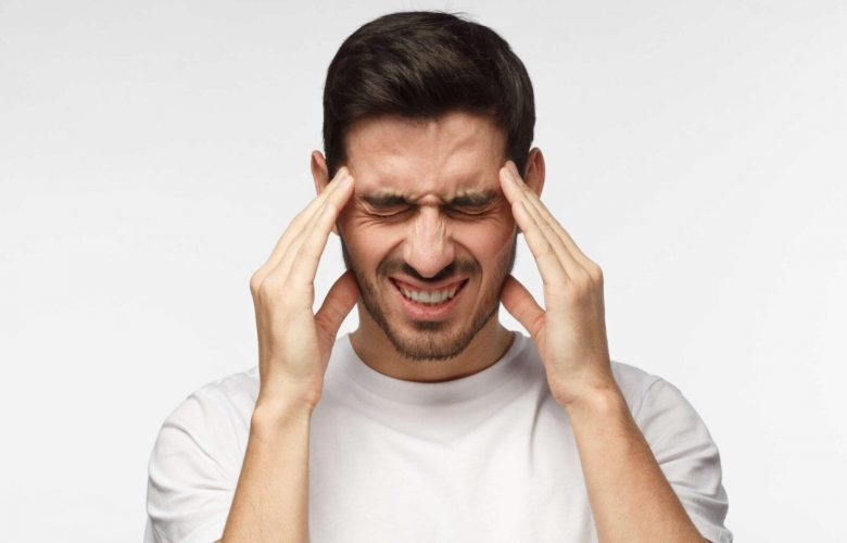 man holding both sides of face with headache