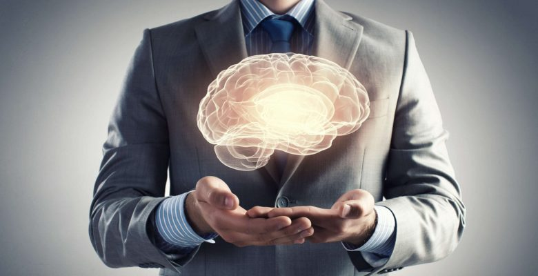 businessman cupping hands above illuminated brain