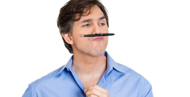 bored man balancing pen on nose