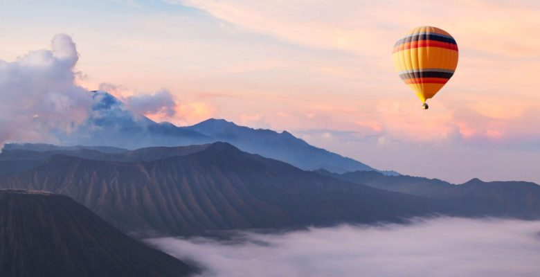 hot air balloon over mountains and clouds
