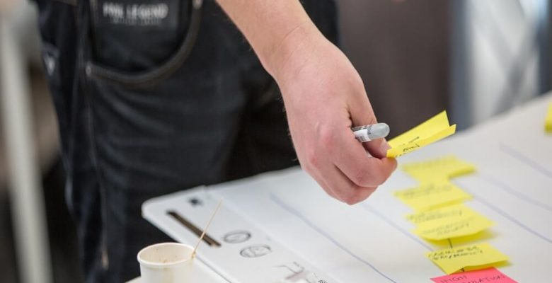 Person holding yellow and white pen writing on white paper