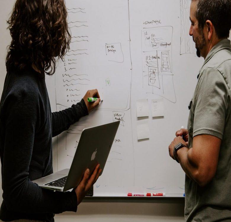 Man wearing grey polo shirt beside whiteboard