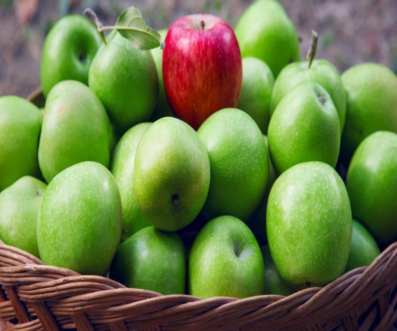 One red apple in a group green apples in basket