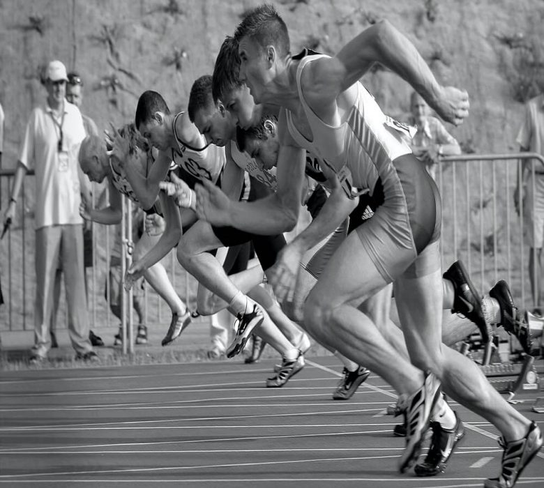 athletes running on track and field oval in greyscale