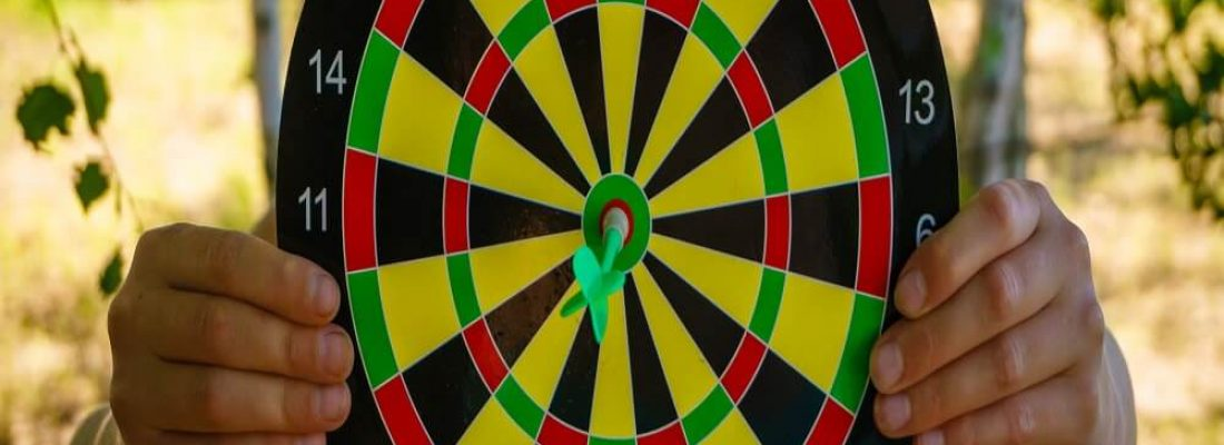 Person holding black, red, yellow and green dart board