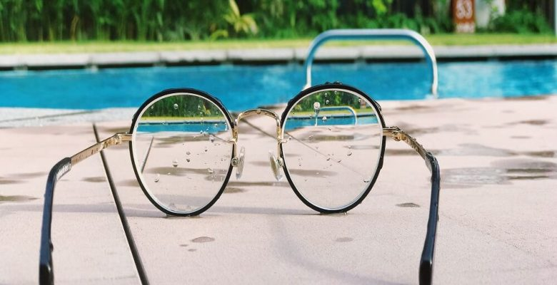 Eyeglasses with black frames on cement by pool