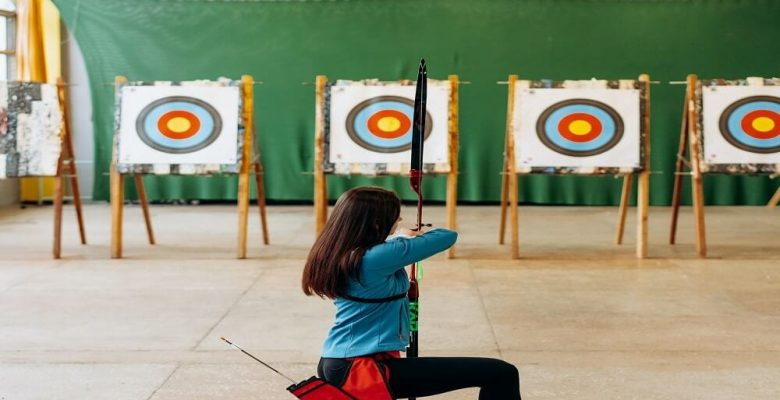 Woman with archery bow choosing from four targets