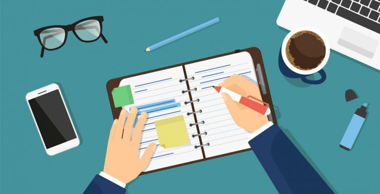 businessman writing in diary at organised desk