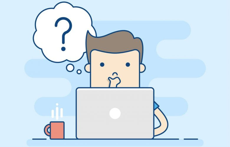 man pausing in front of computer with questions