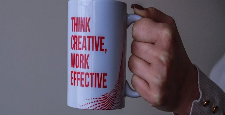 White and red ceramic mug with think creative, work effective text